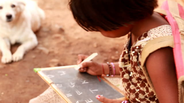 Cheerful Rural Indian girl writing learning ABC