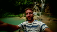 Cheerful travel man takes selfie by the waterfalls