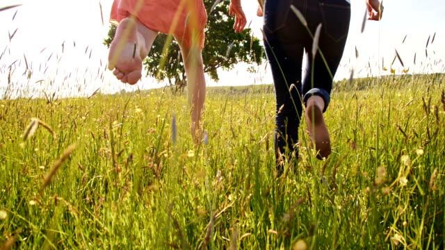 SLO, MO, fröhliche Frau und Mädchen laufen barfuß im Gras