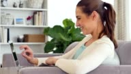 Cheerful woman uses a laptop while relaxing at home