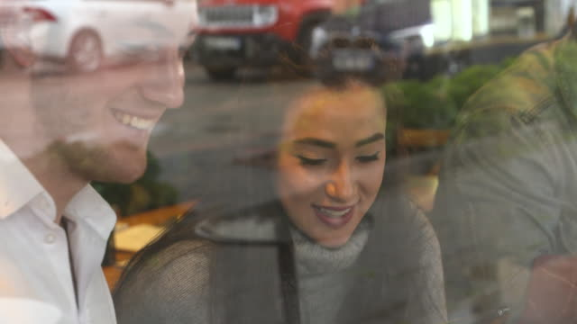 4K: Cheerful young couple in the coffee shop