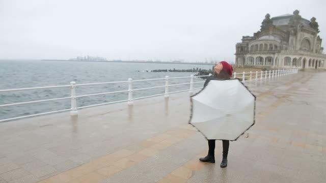 Allegra giovane donna ballando con un ombrello in una giornata di pioggia.