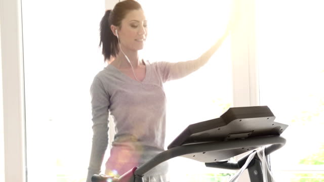 Cheerful young woman exercising on treadmill at home