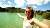 Cheerful young woman takes a selfie portrait by the lake
