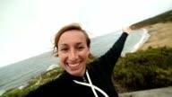 Fröhliche Junge Frau nimmt eine selfie-Porträt auf Glocken Strand
