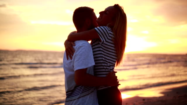 Cheering couple being affectionate on beach at sunset