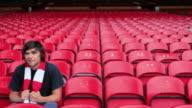 Cheering football fan in empty stadium