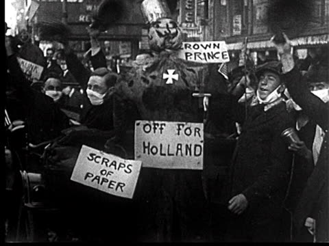 B/W 1918 cheering people with masks standing around effigy of German in Liberty Loan Parade / newsreel