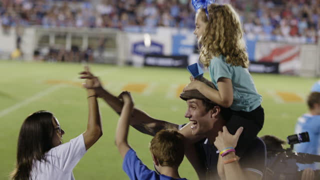 MS. Cheering sports fan with little girl on shoulders high fives friends at professional soccer game.