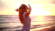 Cheering woman open arms to sunset at seaside