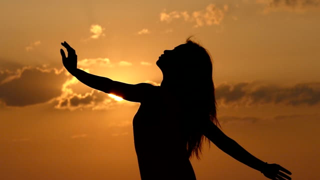 Cheering woman open arms under sunrise on beach slowmotion