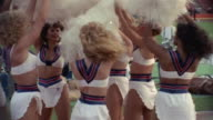 1985 MS USFL cheerleaders doing routine as member of Tampa Bay Bandits stands on field in background/ USA