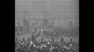 [VO cheers throughout] Royal carriage bearing King George V and Queen Mary approaches as it leaves Buckingham Palace crowds cheer wave members of the...