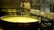 Cheese maker stirring milk for Ricotta cheese production in a large cauldron