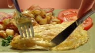 CU cheese omelette with breakfast potatoes on a plate as knife slices through thick omelette and a fork picks up a piece