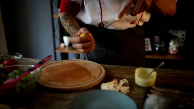 Chef adding lemon to Caesar salad dressing