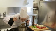 Chef adding pepper to pot
