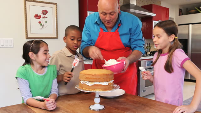 MS ZI ZO Chef and children (6-11) decorating cake / Los Angeles, California, USA