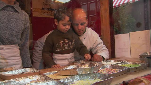 MS PAN Chef and children preparing food at Christmas Market (Kinderweihnacht) / Nuremberg, Bavaria, Germany