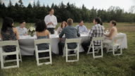 Chef and dinner party guests in a field