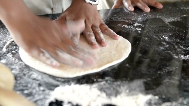 Chef baker making pizza at kitchen