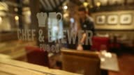 A Chef Brewer Pub Co logo sits on the wall outside The Yew Tree pub operated by Chef and Brewer a unit of Spirit Pub Co in Great Horkesley UK on...