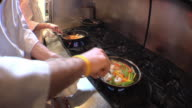 MS SHAKY ZI Chef cooking food on stove in restaurant's kitchen / Chelsea, Michigan, USA