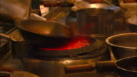 A chef cooks food in a wok over an open flame.