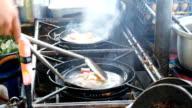 Koch kocht mit einer Pfanne bei einem Feuer-Stock-Videos
