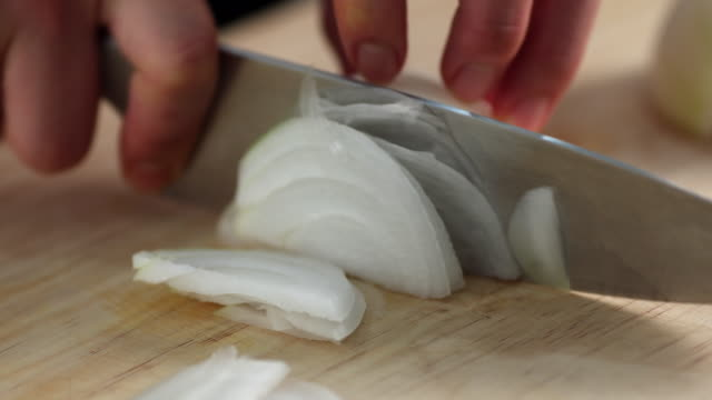 Chef cutting the onion at cutting board