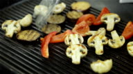 Chef is frying vegetables on the grill.