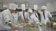 Chef observing his student chop a tomato  in class