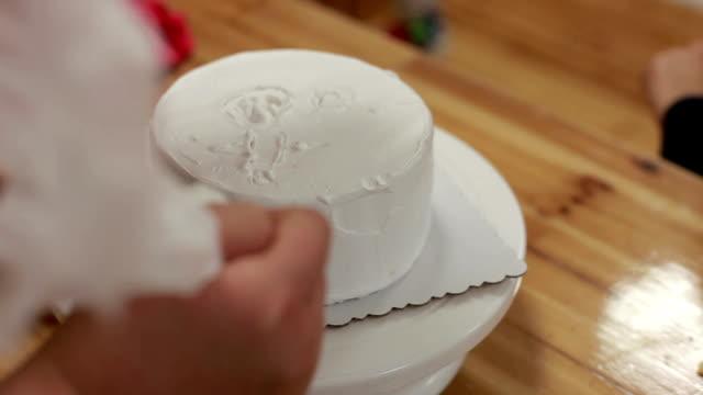 chef piping cream on birthday cake to make swirl decoration