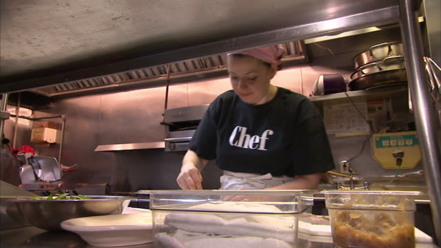 A chef prepares food in the kitchen of a New York City restaurant.