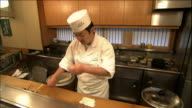 A chef prepares sushi ovals.