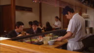 MS, Chef preparing food in sushi bar, clients in background