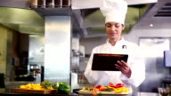 Chef preparing vegetables and using digital tablet
