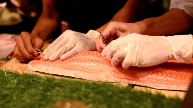Chef pull bone on raw salmon fish, Japanese food culture
