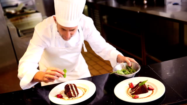 Chef putting mint leaves onto chocolate cake