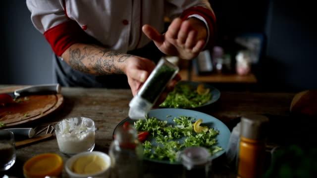 Chef putting oregano on plates