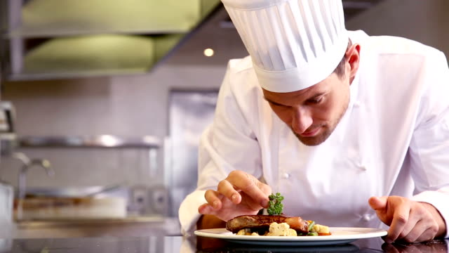 Chef putting parsley on beef dish