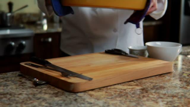 CU, Chef putting roast pork on kitchen bench