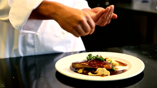 Chef seasoning beef dish
