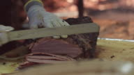 Chef skillfully slices barbecue beef brisket in restaurant kitchen