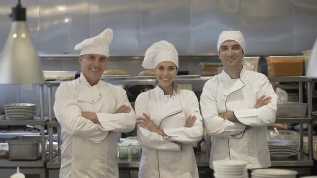 Küchenchef, Sous-Chef und Kochassistenten schaut in die Kamera
