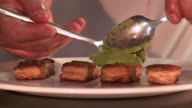 A chef spoons a thick, green paste onto pieces of fish on a white plate. Available in HD.