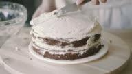 Chef spread cream on model cake