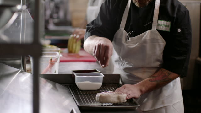 Chef sprinkles salt over raw steak in busy restaurant kitchen