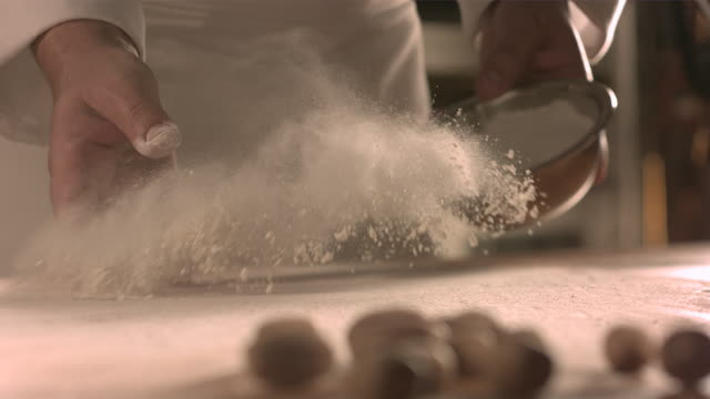 Chef tossing flour onto kitchen table.