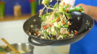 Chef tossing vegetables in wok, slo mo